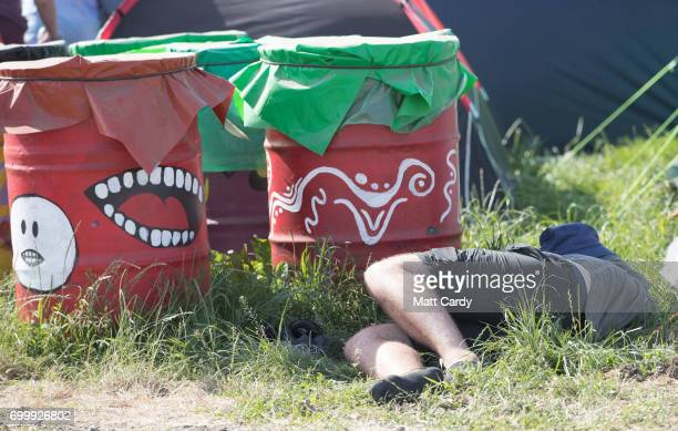 A man sleeps at the Glastonbury Festival site at Worthy Farm in Pilton on June 22 2017 near Glastonbury England The largest greenfield festival in...