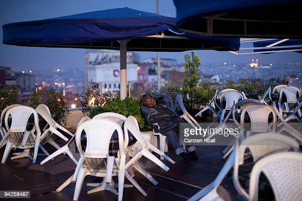 Man sleeps at the morning between chairs in a closed restaurant on October 20, 2009 in Istanbul, Turkey. The Turkish metropolis on the Bosphorus, in...