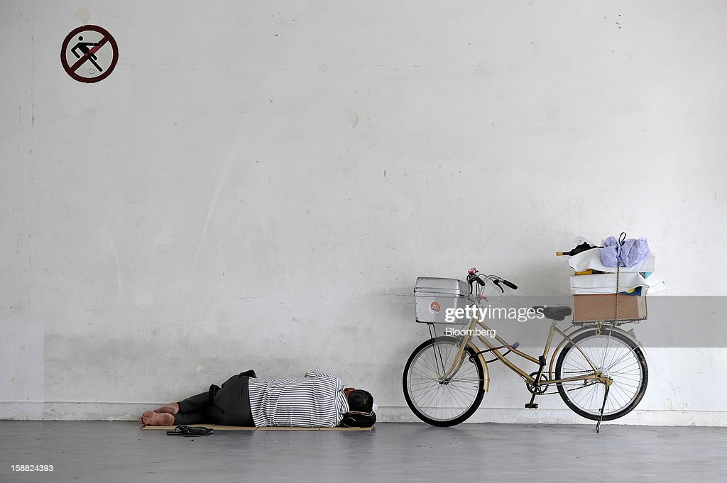 A man sleeps at the void deck of a Housing & Development Board (HDB) apartment block in Singapore, on Sunday, Dec. 30, 2012. Singapore may grapple with elevated inflationary pressures for a third year in 2013, reducing scope for the central bank to provide stimulus to an economy that probably entered a technical recession this quarter. Photographer: Munshi Ahmed/Bloomberg via Getty Images