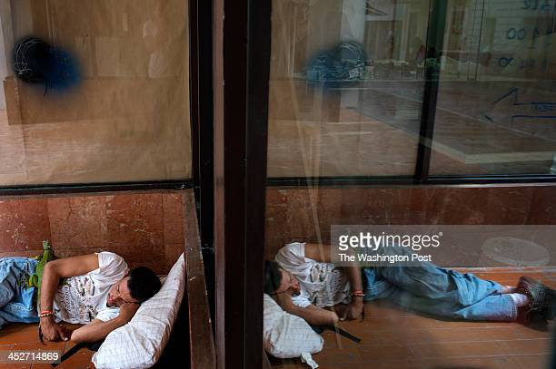 A man sleeps curled up with his iguana outside a store in Old San Juan Puerto Rico on Thursday November 21 2013 Burdened by high unemployment a...