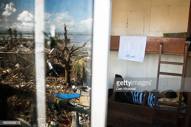 A man sleeps in a cabin on a tanker in a particularly badly damaged part of Tacloban on November 18 2013 in Leyte Philippines Several families who...
