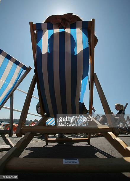 A man sleeps in a deckchair as people gather on Weymouth beach on July 23 2008 in Weymouth England With the majority of schools breaking up this week...