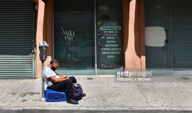 A man sleeps in front of closed shopfronts in what would be a normally busy fashion district in Los Angeles California on May 4 2020 California...