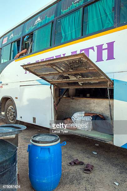 Man sleeps in the luggage compartment of a bus while his passengers shop for textiles outside of Bhuj in Gujarat.