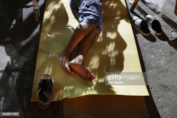 A man sleeps in the parking lot of the apartment building where he lived before being evacuated when Hurricane Irma passed through the area on...