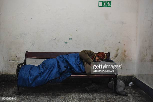 A man sleeps inside the train station as he waits with other migrants and refugees to board a bus in southern Serbian town of Presevo on January 11...