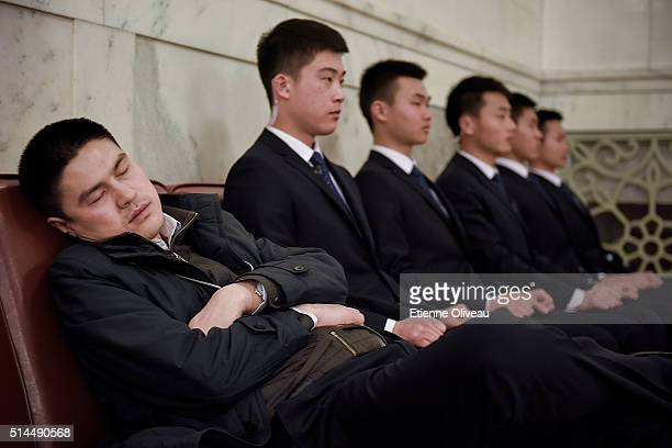 Man sleeps next to civilian guards inside the Great Hall of the People before the Second Plenary Meeting on March 9, 2016 in Beijing, China. The 12th...