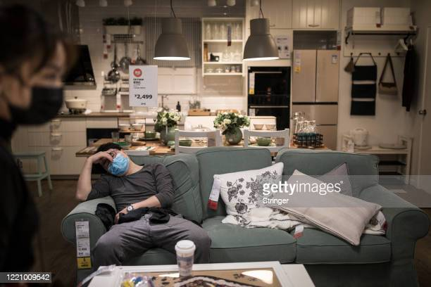 Man sleeps on a sofa as a woman walks past in an IKEA store on April 25, 2020 in Wuhan, China. IKEA Wuhan Branch resumed business on April 21.the...