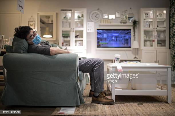Man sleeps on a sofa in an IKEA store on April 25, 2020 in Wuhan, China. IKEA Wuhan Branch resumed business on April 21.the government started...