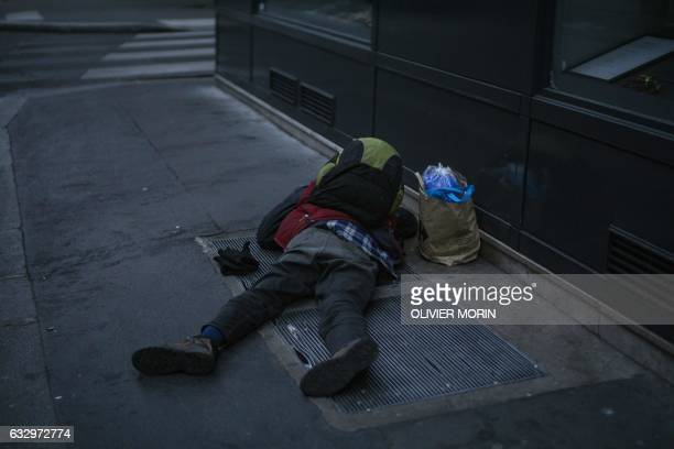 A man sleeps on an air vent to keep warm in a Paris street early on January 29 after a week of unusually low temperatures / AFP / OLIVIER MORIN