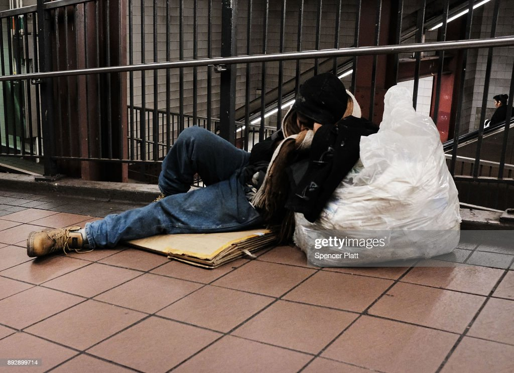 A man sleeps on the ground at a Manhattan train station on December 14, 2017 in New York City. According to a new report released by the U.S. Department of Housing and Urban Development New York City's homeless population expanded by about 4 percent in 2017 as the number of homeless people nationwide grew to about 553,000.