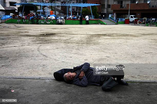 A man sleeps on the ground in the slum area of Kamagasaki on April 23 2016 in Osaka Japan Kamagasaki a district in Japan's second largest city Osaka...