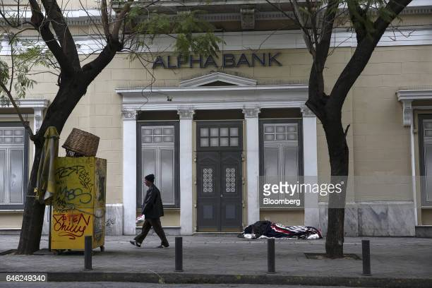 A man sleeps on the street outside a closed Alpha Bank AE bank branch in Athens Greece on Tuesday Feb 28 2017 Greeces auditors are pulling together a...