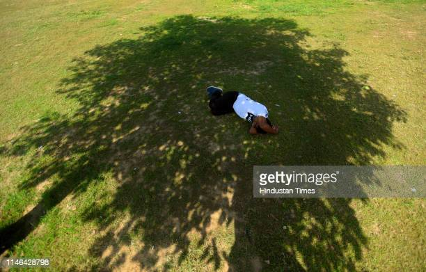 Man sleeps under the shade of a tree on a hot summer day, near Rajpath, on May 27, 2019 in New Delhi, India.
