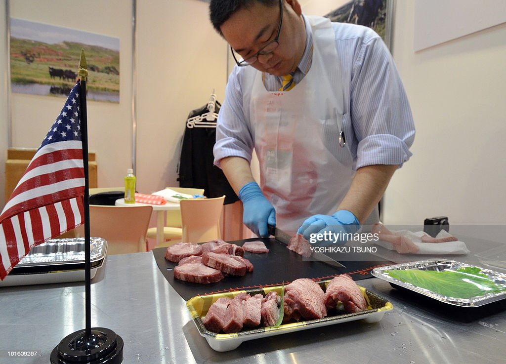 A man slices American beef to display at the annual supermarket and trade show in Tokyo on February 13, 2013. Japan has eased restrictions on beef imposed due to concerns over mad cow disease, easing a decade-long row between the allies. Japan, formerly the largest buyer of US beef, had agreed to allow the import of the meat from cattle slaughtered at up to 30 months old, higher than the earlier safety limit of 20 months. AFP PHOTO / Yoshikazu TSUNO