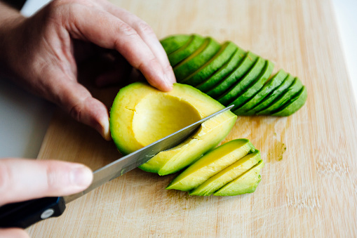 Man slicing avocado with a knife on a cutting board close up - gettyimageskorea