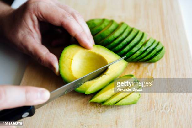 man slicing avocado with a knife on a cutting board close up - chop stock pictures, royalty-free photos & images