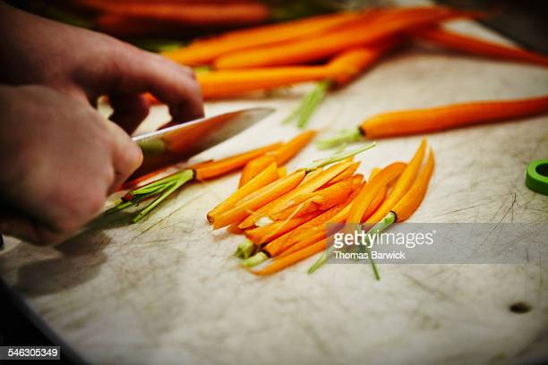 Man slicing carrots on cutting board in kitchen