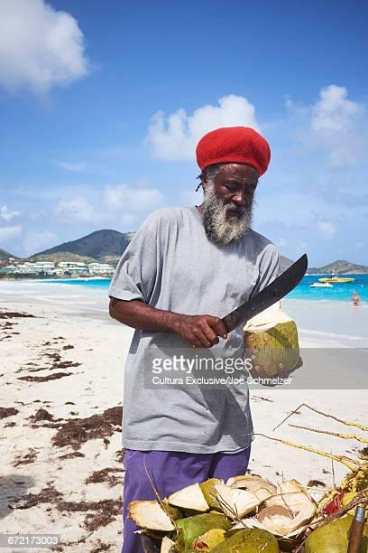 Man slicing coconuts on beach, Saint Martin, The Caribbean