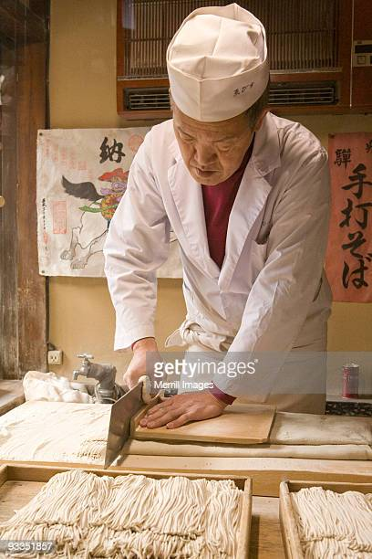 man slicing dough to make soba noodles - soba stock pictures, royalty-free photos & images