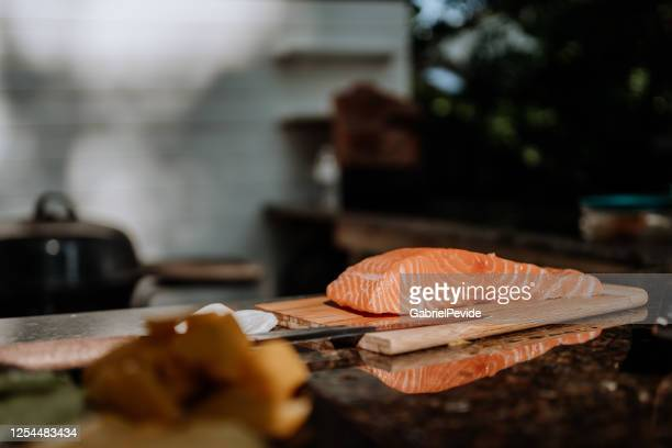 man slicing salmon - raw food stock pictures, royalty-free photos & images