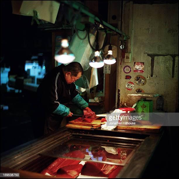 CONTENT] Man slicing tuna at Tsukiji fish market Tokyo