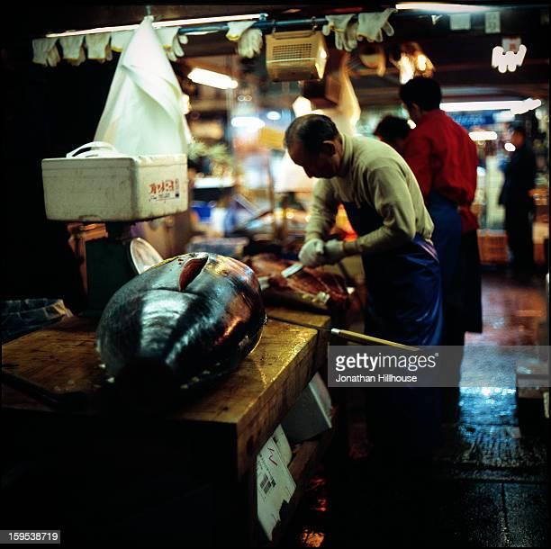 CONTENT] Man slicing tuna Tsukiji fish market Tokyo Japan
