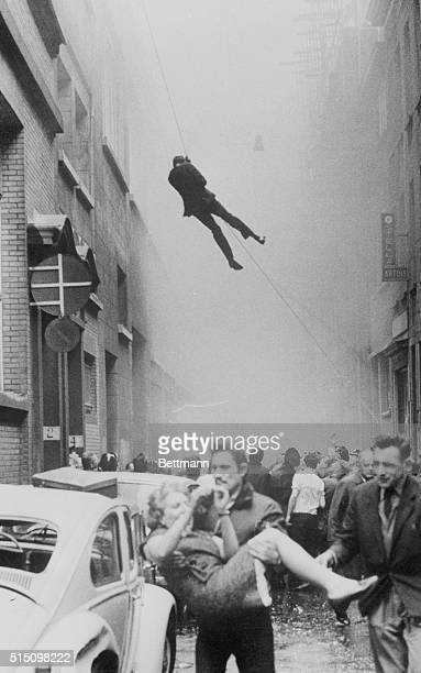 A man slides down a rope and a woman is carried from the scene of a fire which destroyed L'Innovation the second largest department store in Brussels...