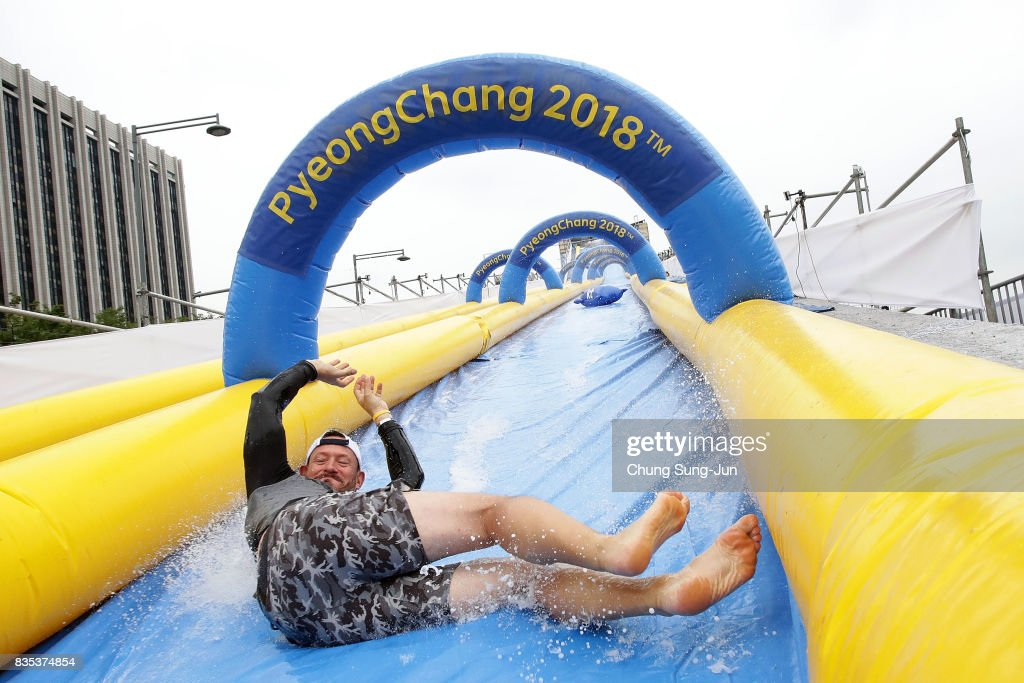 A man slides down on an inflatable bobsleigh during the 'Bobsleigh In the City' on August 19, 2017 in Seoul, South Korea. The 22-metre-high 300-metre-long water slider has been set up in the central Seoul to promote upcoming PyeongChang Winter Olympics.