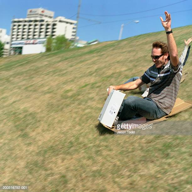 man sliding down grassy hill on cardboard - jason todd stock photos and pictures