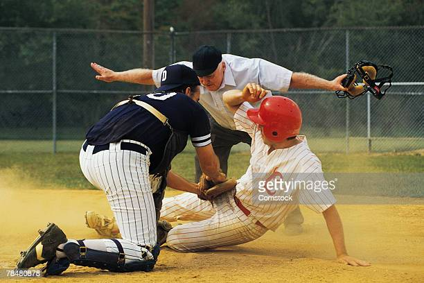 man sliding into home plate - referee stock pictures, royalty-free photos & images