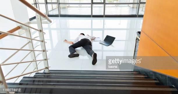 l'homme glisse tombant sur le plancher mouillé dans un bâtiment de bureau moderne. - lying down photos et images de collection
