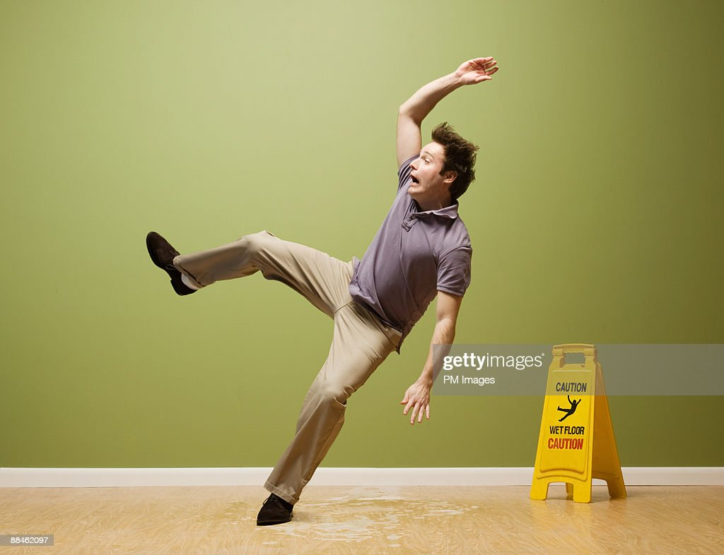Man slips on wet floor : Stock Photo