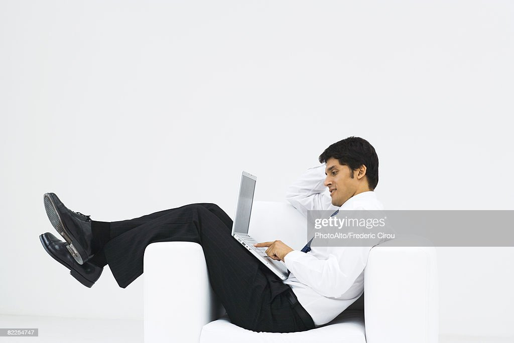 Man slouching in armchair, using laptop, side view : Stock Photo