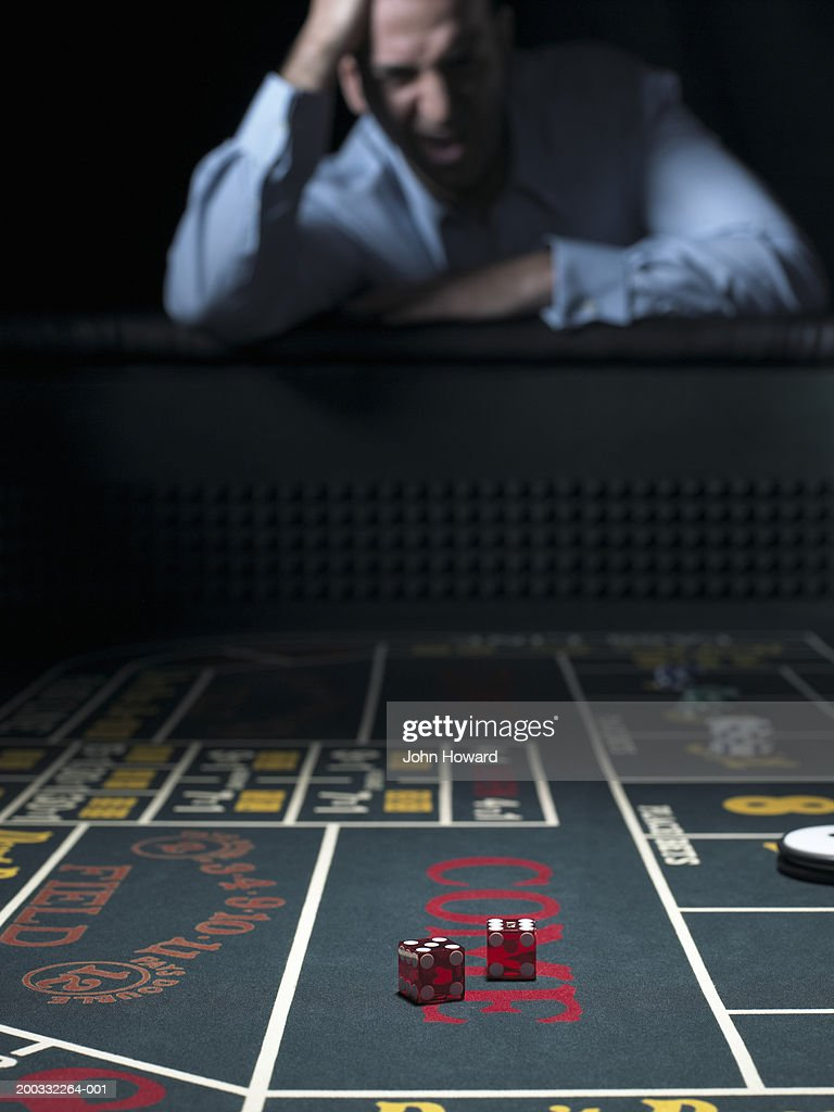Man slumped at craps table, holding head (focus on table) : Stock Photo