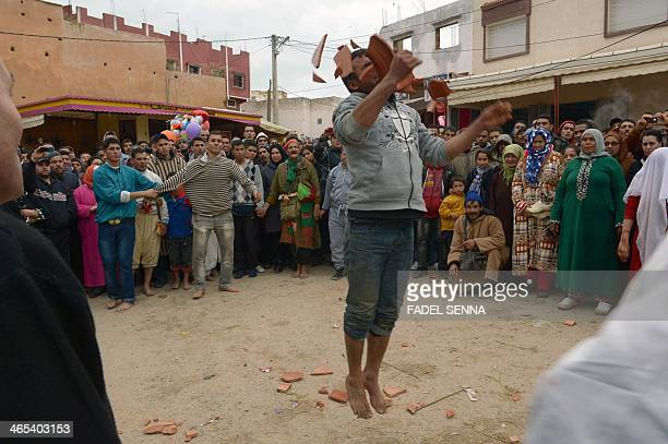 A man smashes a large terracotta plate with his head during the festival of Sidi Ali Ben Hamdouch on January 21 2014 in the Moroccan village of Sidi...