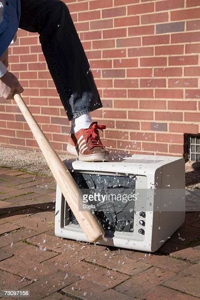 man smashing a monitor with a baseball bat - demolishing stock pictures, royalty-free photos & images