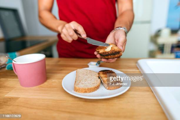man smearing butter on toast - toasted bread stock pictures, royalty-free photos & images