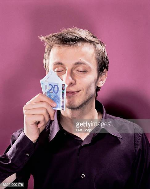 man smelling 20 euros - twenty euro banknote stock photos and pictures