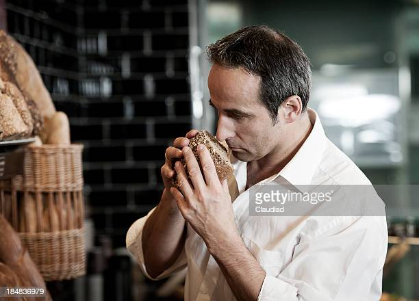 Man smelling at bread in supermarket