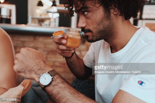 Man Smelling Drink In Container