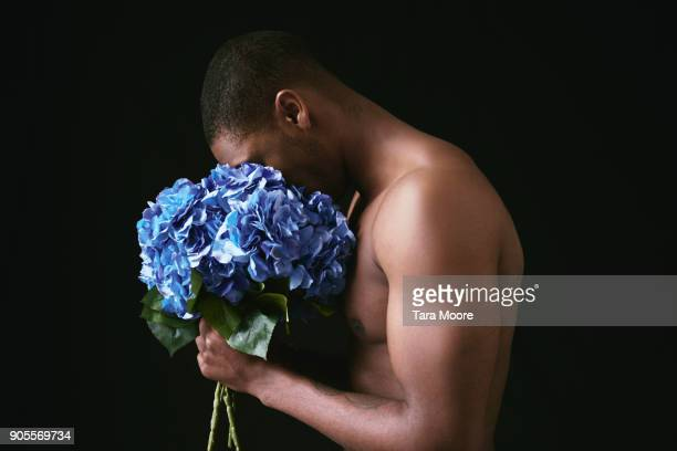 man smelling flowers - männlichkeit stock-fotos und bilder