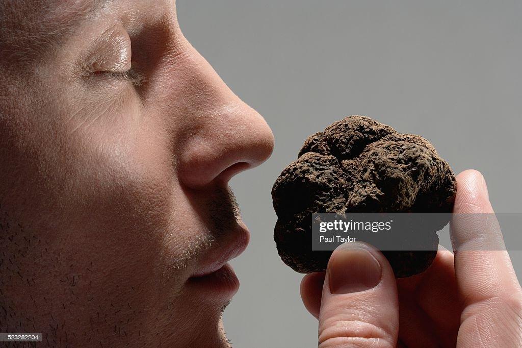 Man smelling mushroom truffle : Stock Photo