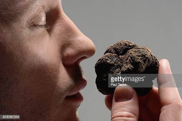 man smelling mushroom truffle - nose stock pictures, royalty-free photos & images