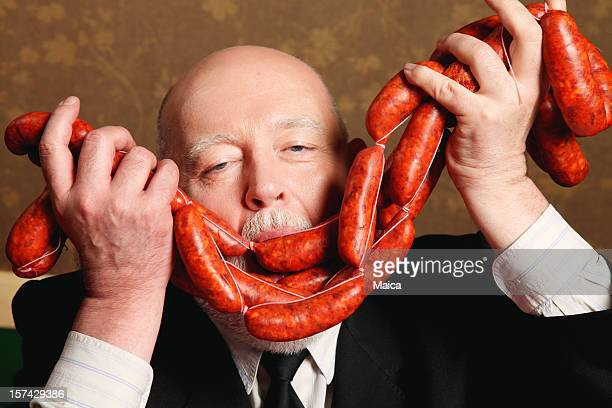 Man smelling red sausages