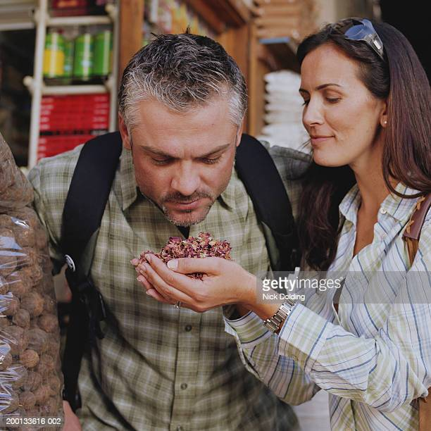 Man smelling spices held by woman