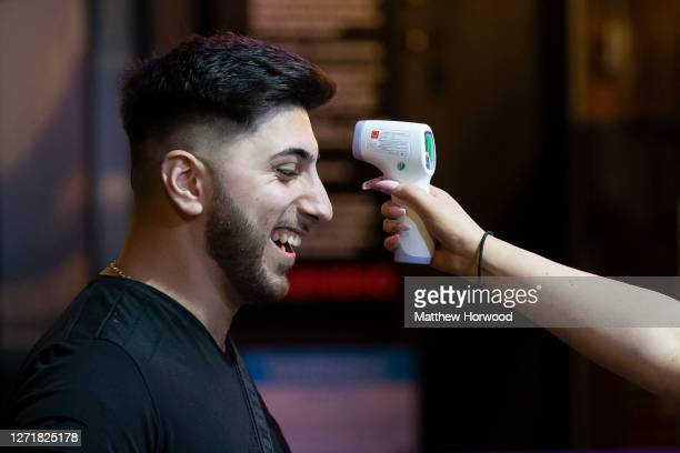 Man smiles as he has his temperature checked before entering the Coyote Ugly bar on St. Mary's Street on September 10, 2020 in Cardiff, Wales. In a...