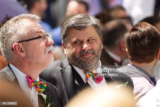 A man smiles at his fianacee during the Grand Pride Wedding a mass gay wedding at Casa Loma in Toronto Canada on June 26 2014 The celebration which...