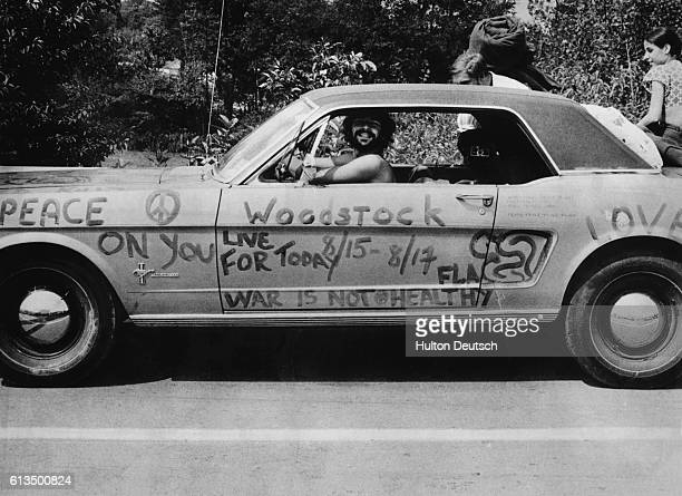 A man smiles from the inside of his Ford Mustang which has been tagged with various peace and antiwar messages in Bethel New York on his way to the...
