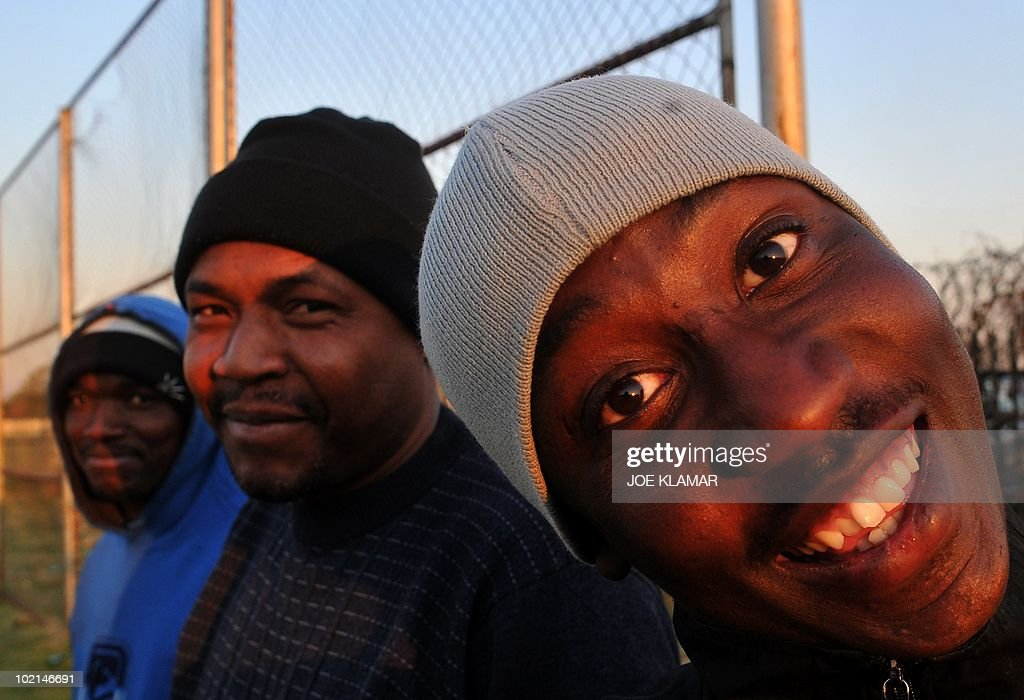 A man smiles in a camera as he watch his friends to play football at Mamelodi township in Pretoria on June 16, 2010 during the 2010 World Cup football tournament in South Africa.